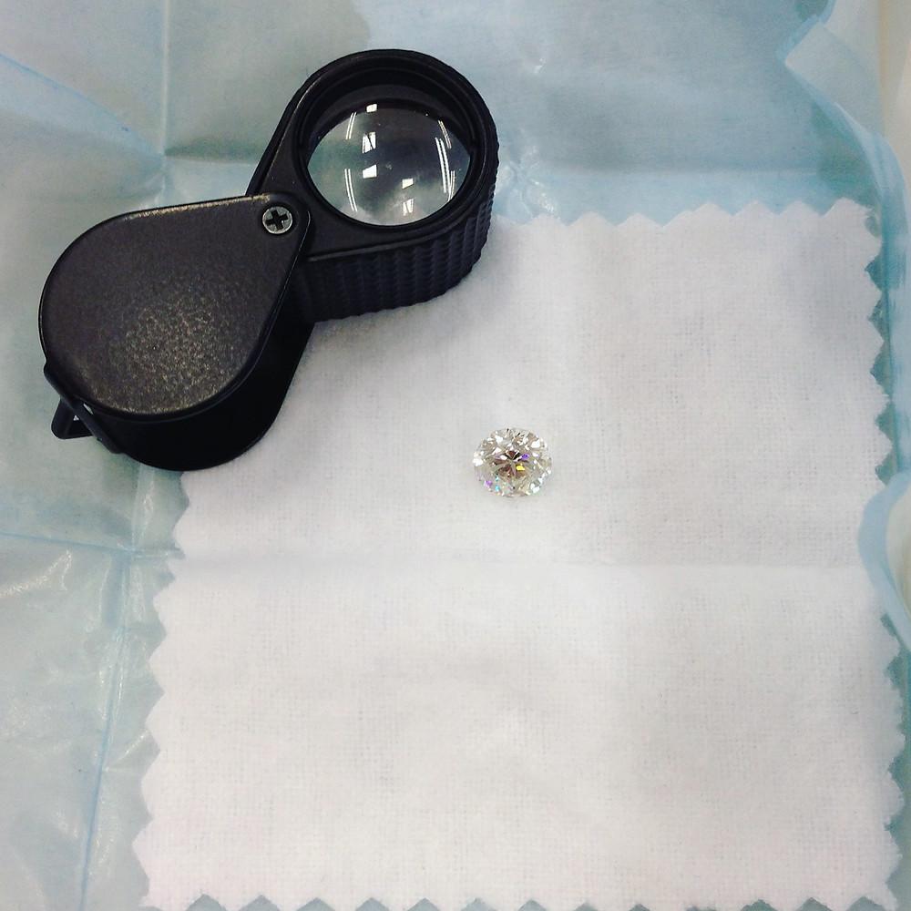 round diamond in a brifka next to a black jeweler's loupe