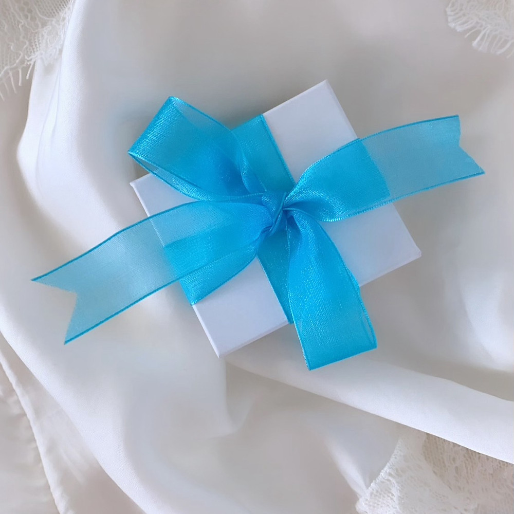 a white jewellery box with a blue ribbon tied in a bow, on a white silk background by Tsarina Gems