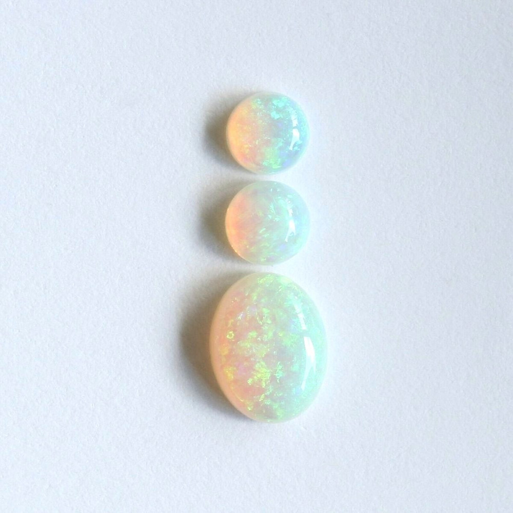 round and oval white opal cabochons showing range of shape and play of colour on white background