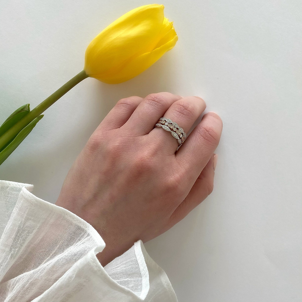 Selection of vintage inspired diamond stacking bands in rose, white gold, by Tsarina Gems, worn on a lady's hand, frilly white blouse, on a white background, next to a yellow tulip flower