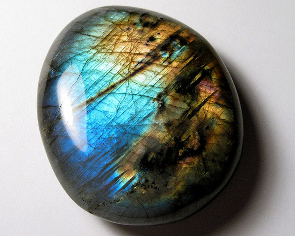 loose free form labradorite showing labradorescence on a white background
