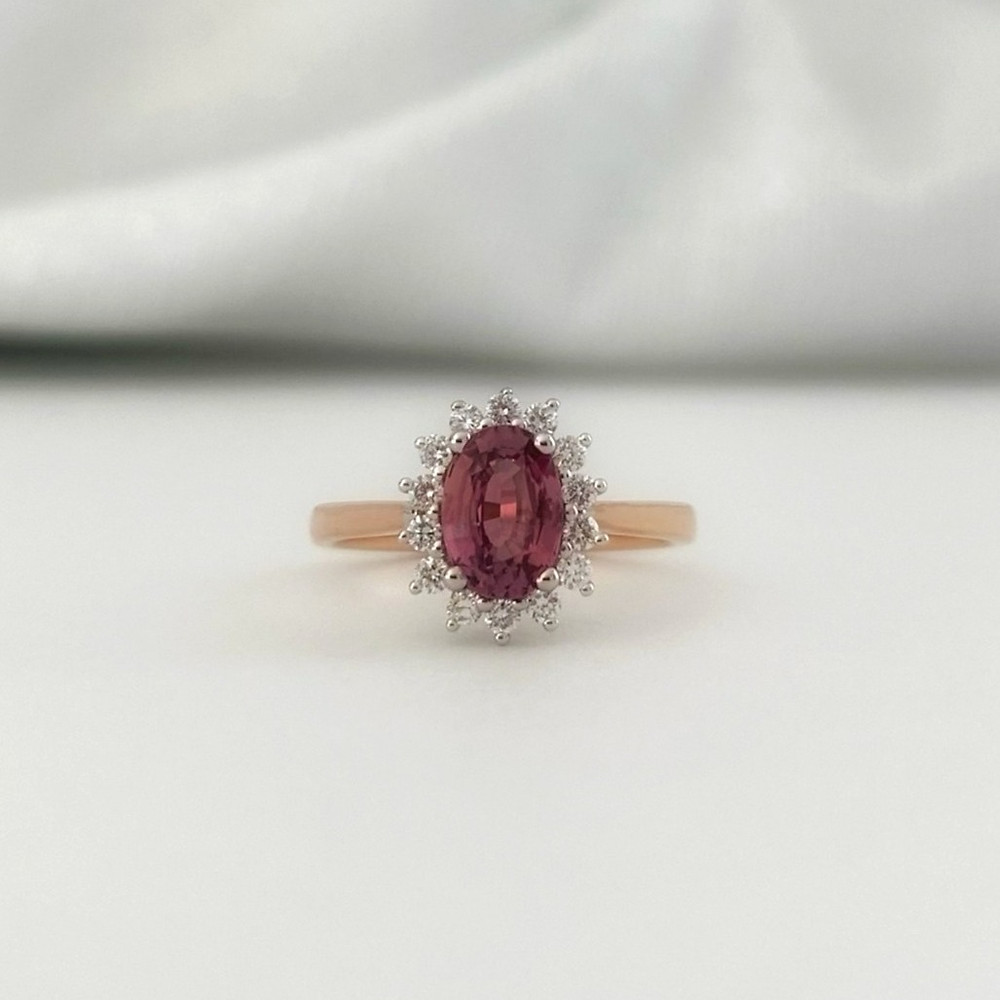 oval padparadscha sapphire diamond halo ring in rose and white gold, vintage inspired engagement ring by Tsarina Gems, on a white background