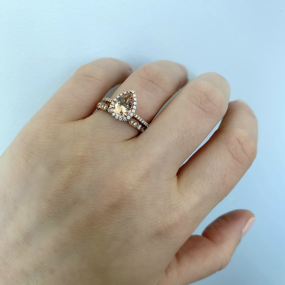 lady's hand wearing a vintage inspired pear shape morganite and diamond halo rose gold engagement ring and wedding band bridal set by Tsarina Gems on a light background
