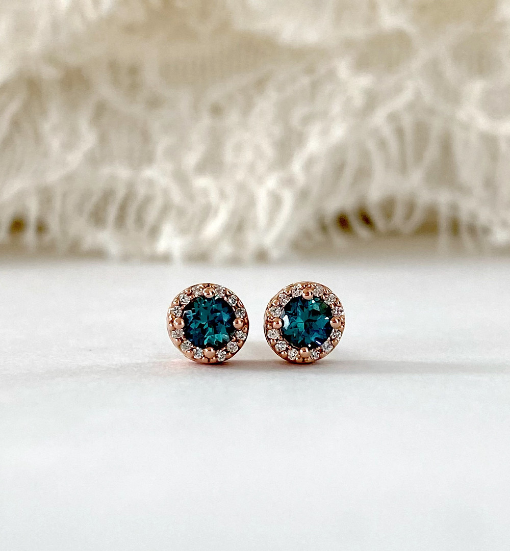 Round alexandrite and diamond halo stud earrings in rose gold with filigree setting, on a white background