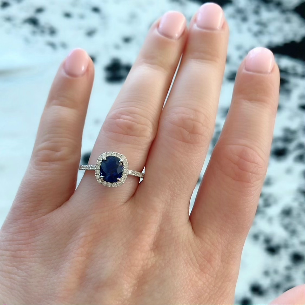 woman's hand wearing a cushion sapphire and diamond halo white gold engagement ring