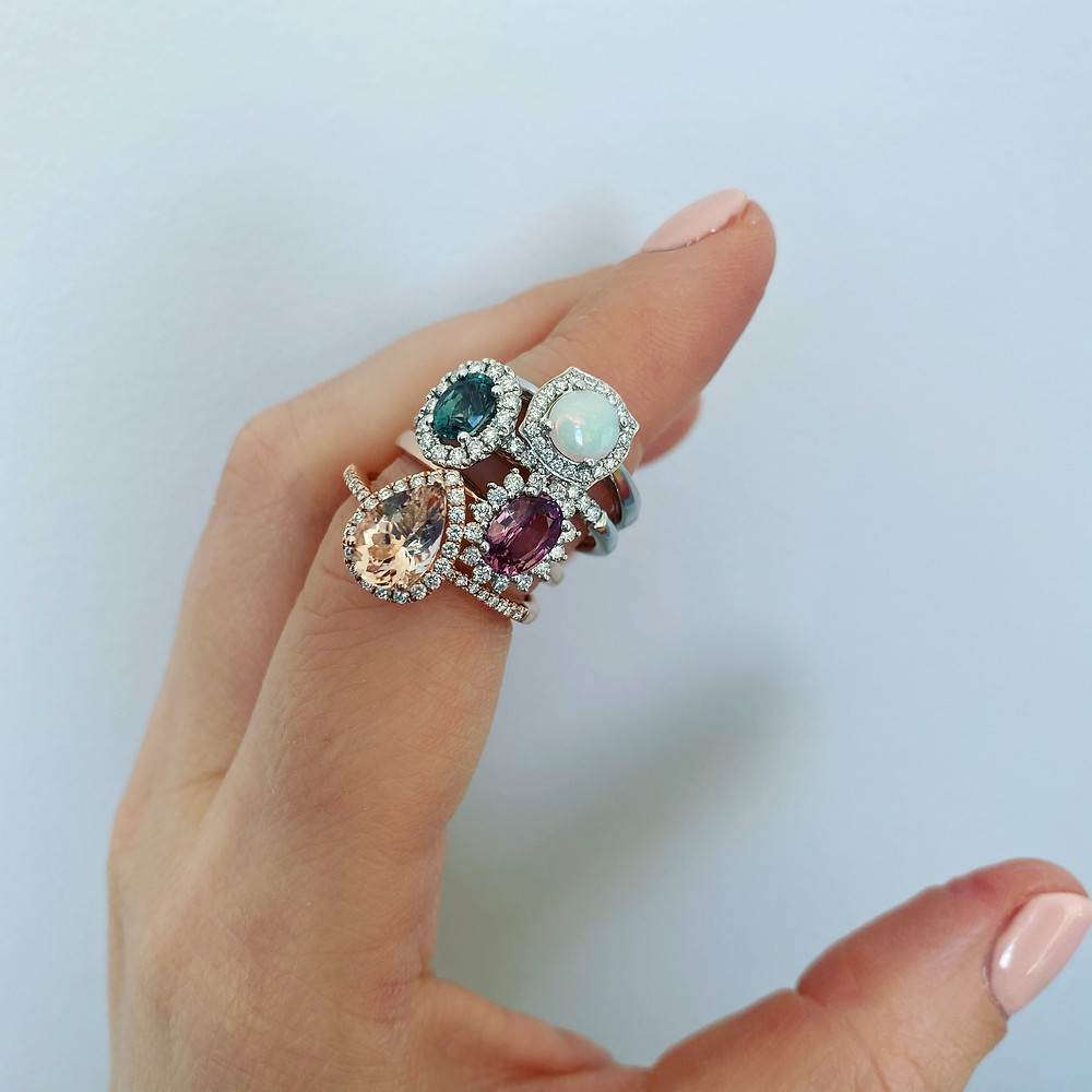 lady's hand wearing vintage inspired engagement rings on index finger by Tsarina Gems, round opal diamond halo white gold ring, oval blue green sapphire diamond halo white gold ring, oval padparadscha sapphire diamond halo rose gold ring, pear morganite diamond halo rose gold ring