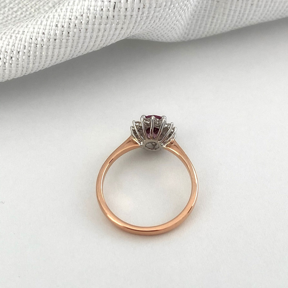 oval orangey pink Padparadscha sapphire vintage inspired diamond halo ring two tone rose gold and white gold on a white background by Tsarina Gems close up of gallery and basket side profile view showing intricate detail