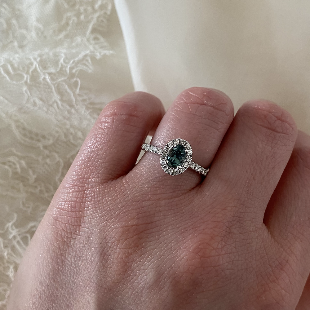 lady's hand wearing oval blue green sapphire and diamond halo white gold engagement ring, teal sapphire engagement ring, mermaid sapphire, peacock sapphire, on a white background, by Tsarina Gems