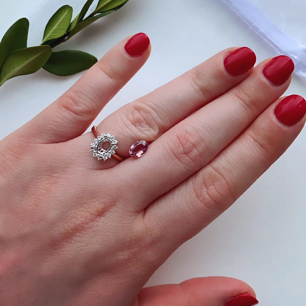 loose orangey pink oval Padparadscha sapphire next to a two tone rose and white gold diamond halo semi mount vintage inspired on a lady's hand with red nails on a white background next to an evergreen