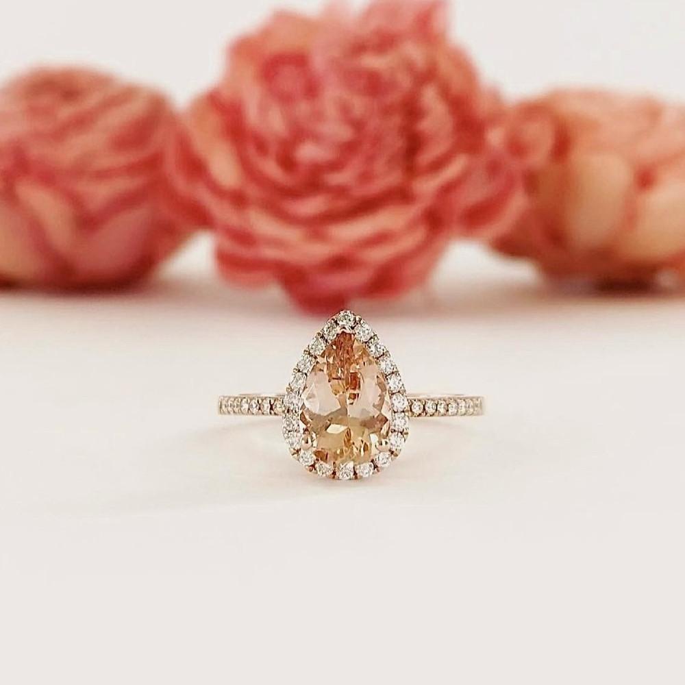 Pear shape morganite and diamond halo rose gold engagement ring next to pink orange flowers
