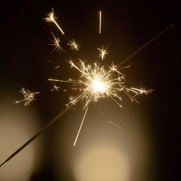 lit sparkler on a dark background