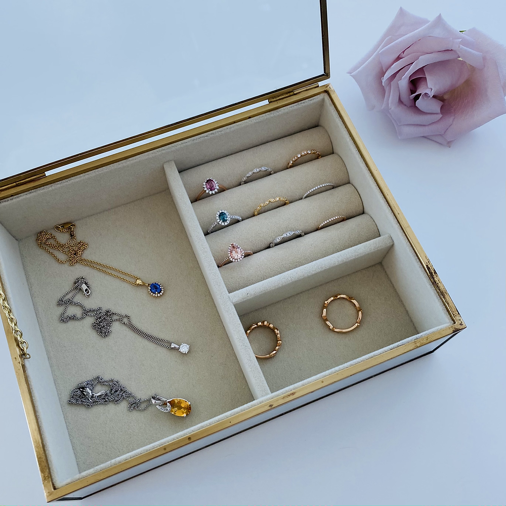 Yellow gold jewellery box with rings and necklaces next to a pink rose