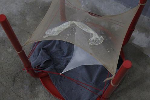 김제이, <Drops>, 스테인레스 스툴, 스타킹, 고무줄, 콘돔, 회색 천, 풍선, 물, 40×40×45cm, 2020