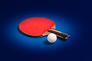 Tabletennis racket and ball on table.jpg