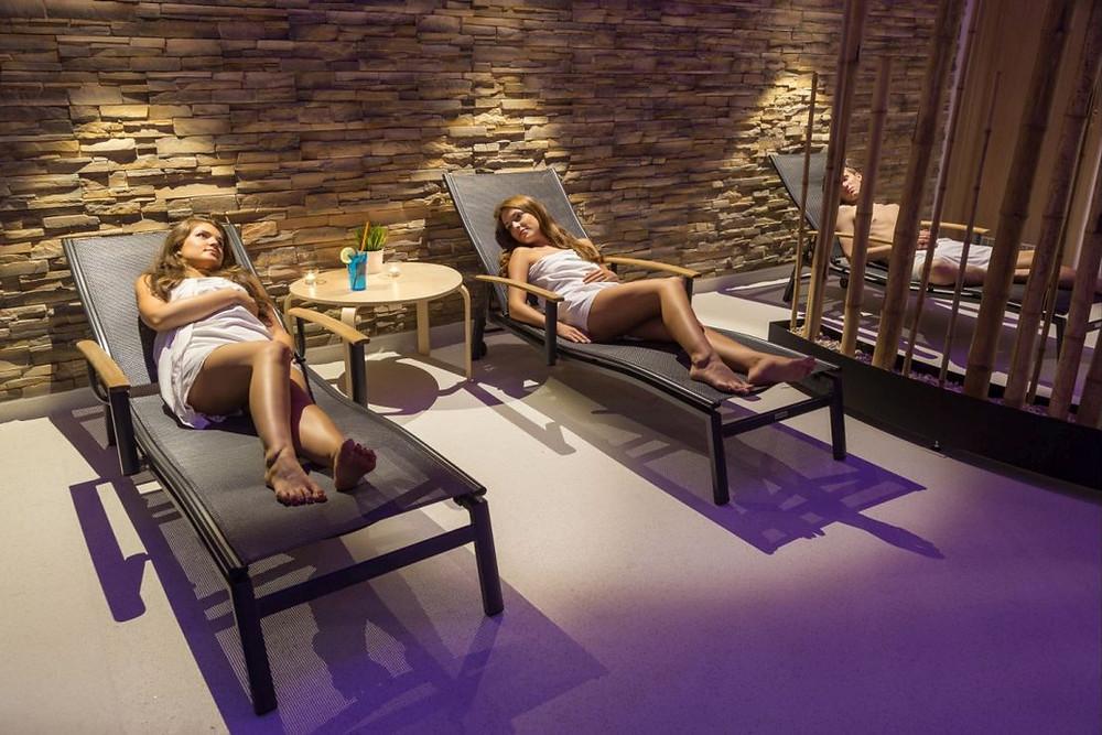 Dvě ženy relaxující na lehátkách po saunování znázorňující, jak se v sauně chovat správně