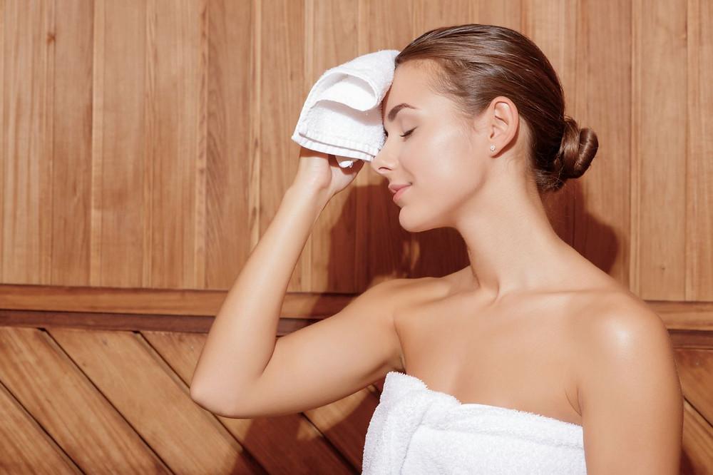 Mladá žena v sauně sušící si čelo ručníkem jako znázornění tématu, kdy chodit do sauny