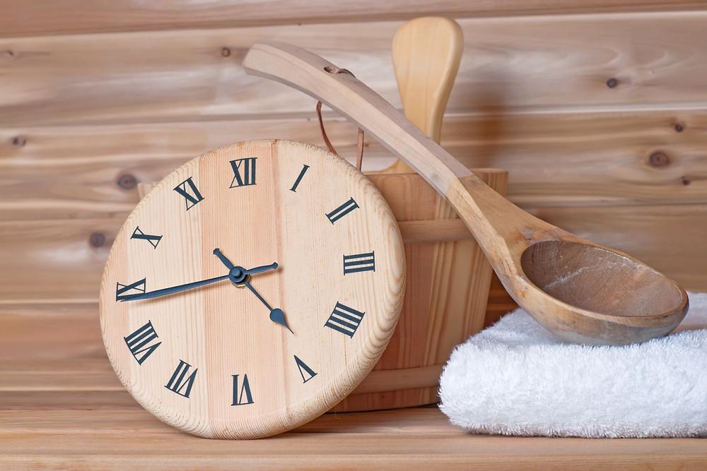 Dřevěné hodiny do sauny s vědrem a lžící na polévání kamenů.