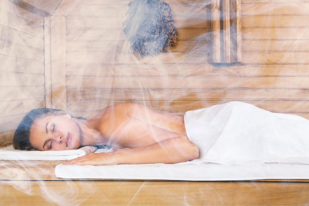 Detoxikace organismu v sauně znázorněná ženou ležící na lavici v obklopení páry.