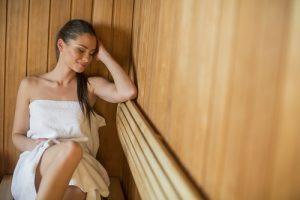 Žena relaxující ve finské sauně zabalená v prostěradle