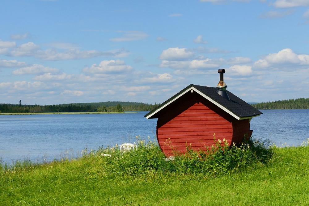 Historie saunování zpodobněná v obrázku finské sauny stojící u vody
