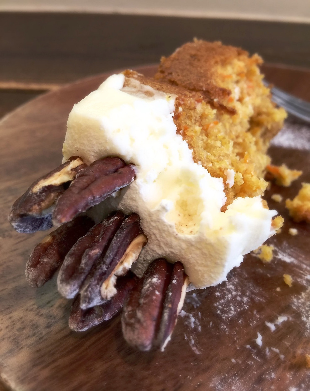 Pecans, cream cheese frosting on carrot cake