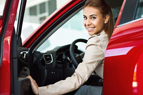 Photo of happy young mixed race woman sitting inside her new car. Concept for car rental.j