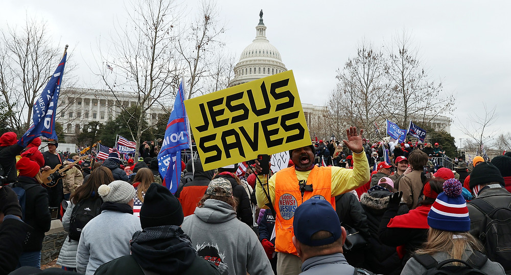 "A yellow banner that reads ""JESUS SAVES"" stands out in the pro-Trump mob outside the U.S. Capitol on Wednesday."
