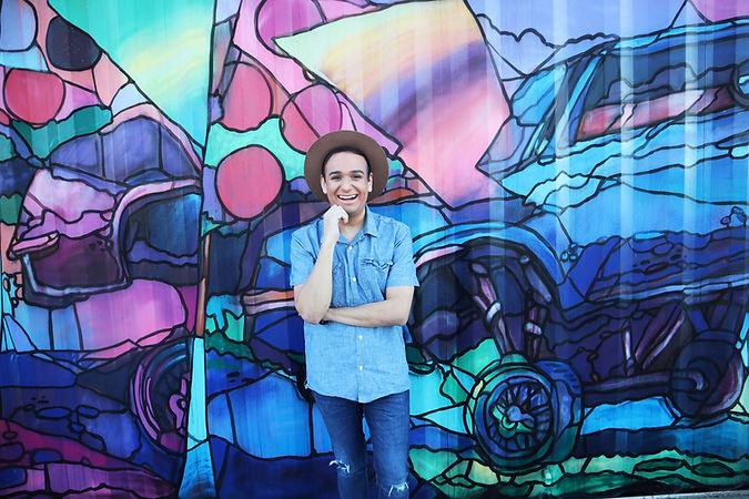 jose cortez standing in front of mural.j