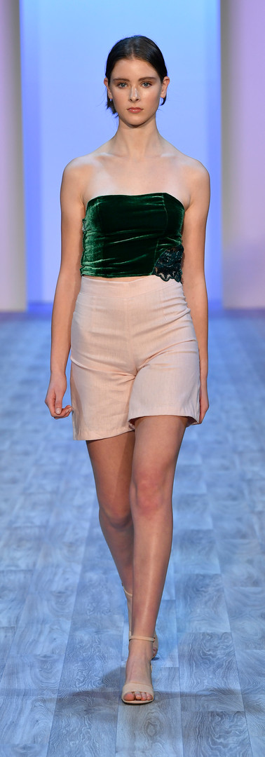 Silk velevt top with half moon cut out with beaded insert. Pink linen high waisted shorts. Photo by Getty Images