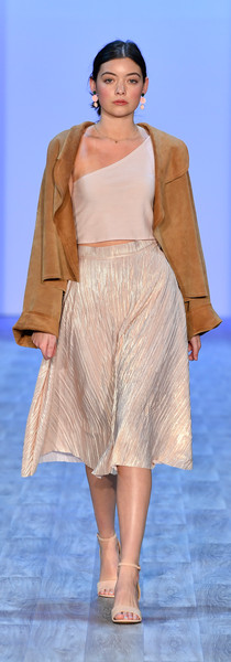 Merino one shoulder crop, lurex knit skirt and real suede crop jacket with velevt embroidered patch. Photo by Getty Images