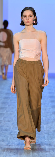 Velevt top with half moon cut out with sequin insert. Wool pinstripe wide legged pant. Photo by Getty Images
