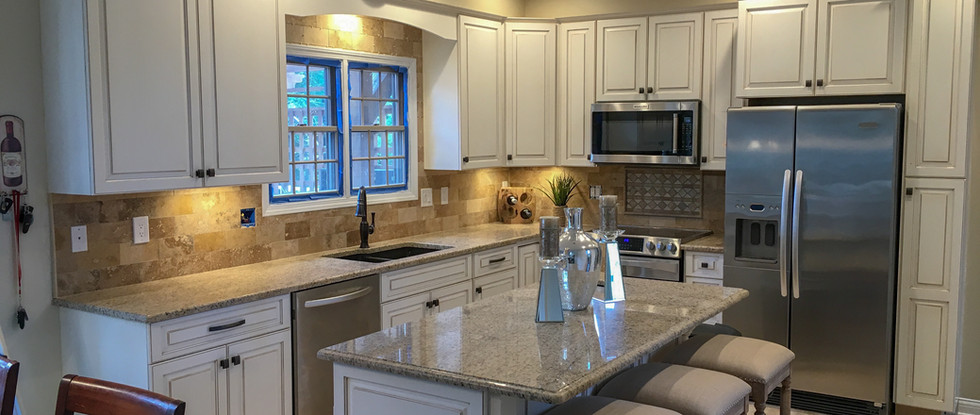 Hand-Painted Maple Antique White with Brown Glaze Cabinets, Custom Island Finishes, Granite Countertops, Travertine Tile Backsplash by Cabinetworks Kitchens