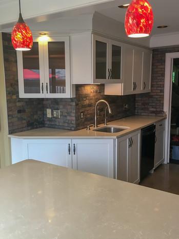 Brick Tile Wall Backsplash, Quartz Countertops, White Shaker Cabinets by Cabinetworks Kitchens