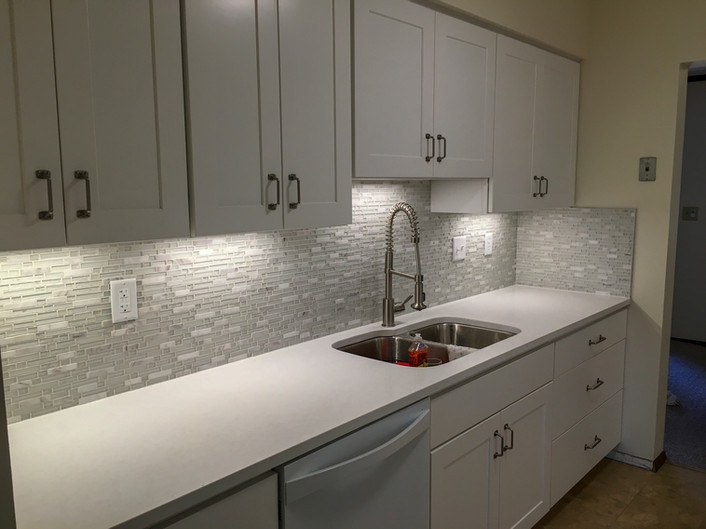 White Shaker Cabinets, Glass Tile Mosaic Backsplash, White Quartz countertops by Cabinetworks Kitchens