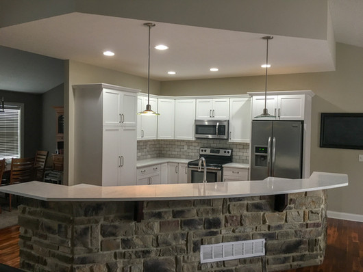White Shaker Cabinets, Marble/Quartz Countertops, Marble Tile Backsplash, Stone Wall by Cabinetworks Kitchens