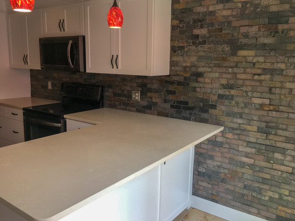 Brick Tile Wall Backsplash, Quartz Countertops, White Shaker Cabinets by Cabinetworks Kitchens