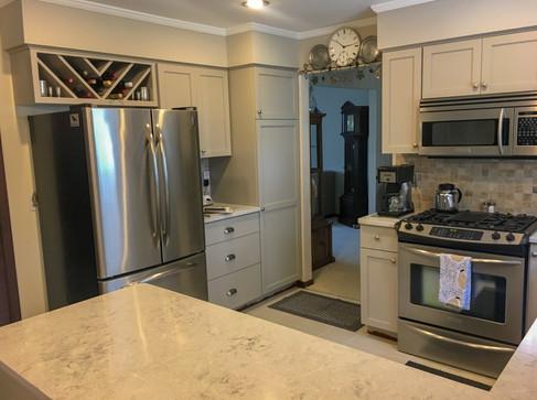 Dove Grey Shaker Cabinets, Custom Wine Rack, Quartz Countertops, Tile backsplash by Cabinetworks Kitchens