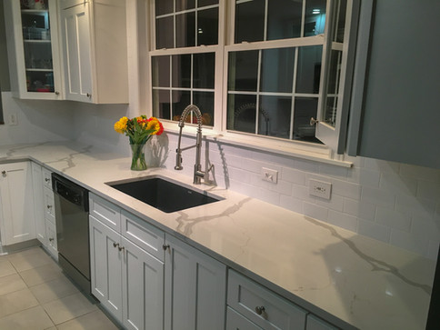 White Double Panel Shaker Cabinets, Marble Look Quartz Countertops, Subway Backsplash by Cabinetworks Kitchens