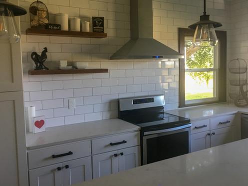 White Shaker Farmouse Cabinets, Marble Quartz Countertops, Open Shelving, Subway Tile Backsplash by Cabinetworks Kitchens