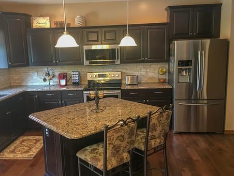 Black Painted Raised Panel Cabinets, Granite Countertops, Travertine Mosaic Tile Backsplash by Cabinetworks Kitchens