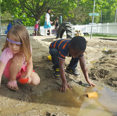 Two children dig in water in the sand area