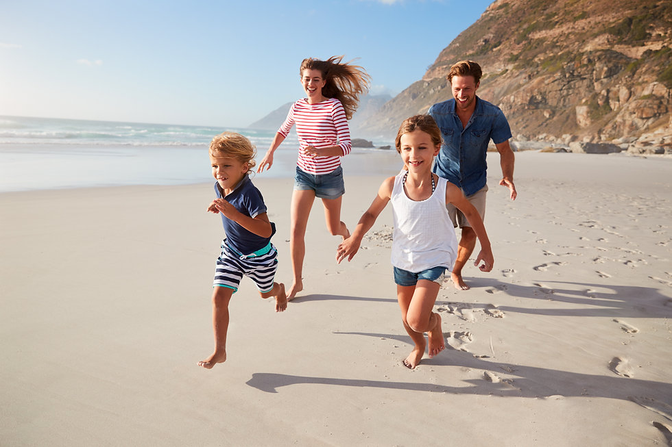 Parents Running Along Beach With Childre
