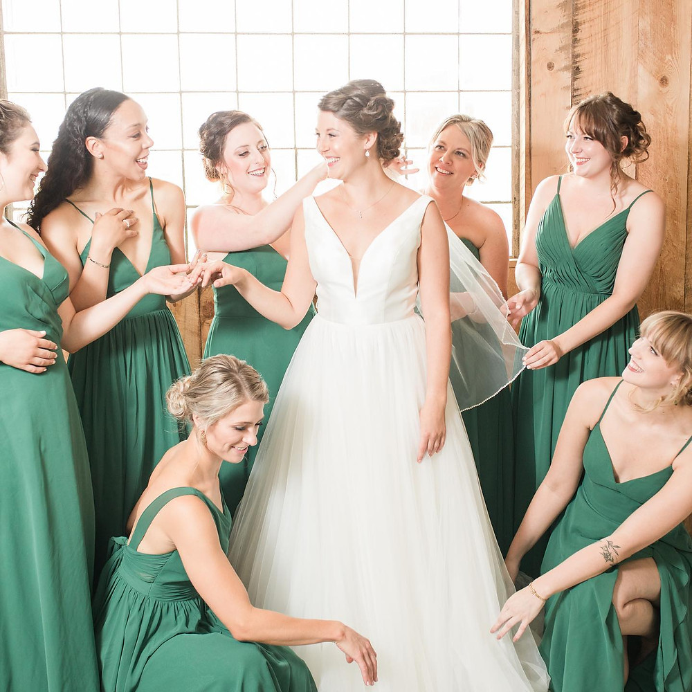 2021 bride is with her bridesmaids, matron of honor in front of the downstairs in the barn. They are standing in front of a large window and rustic wood.