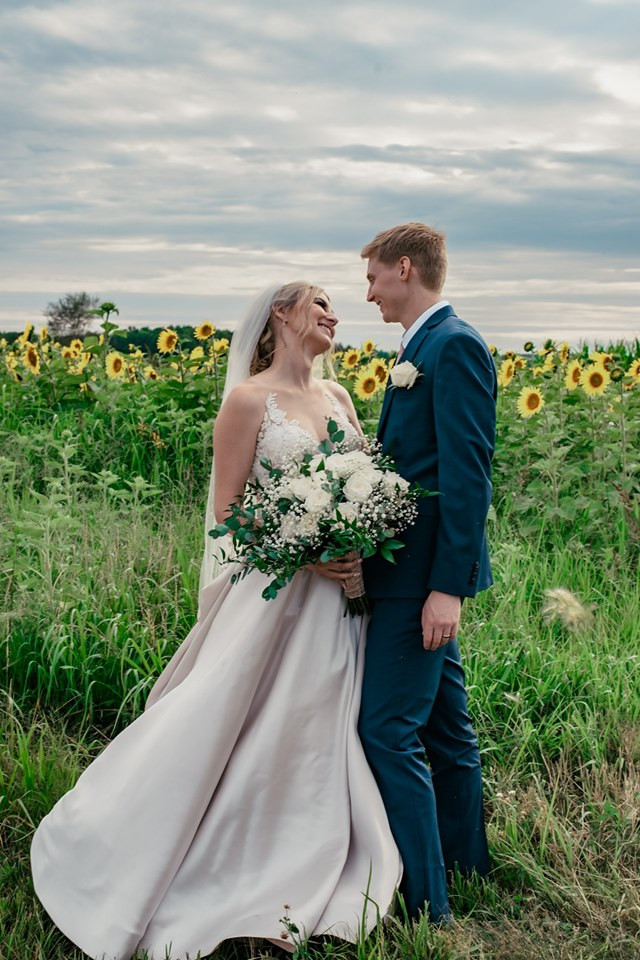 bride and groom by sunflowers