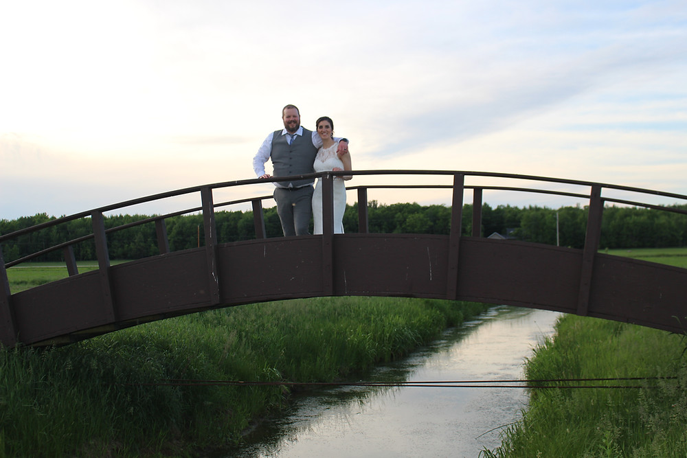 Bride and groom on arched bridge