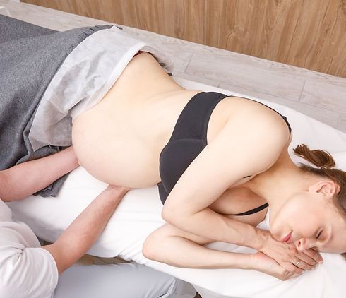 Pregnant woman receiving osteopathic tre