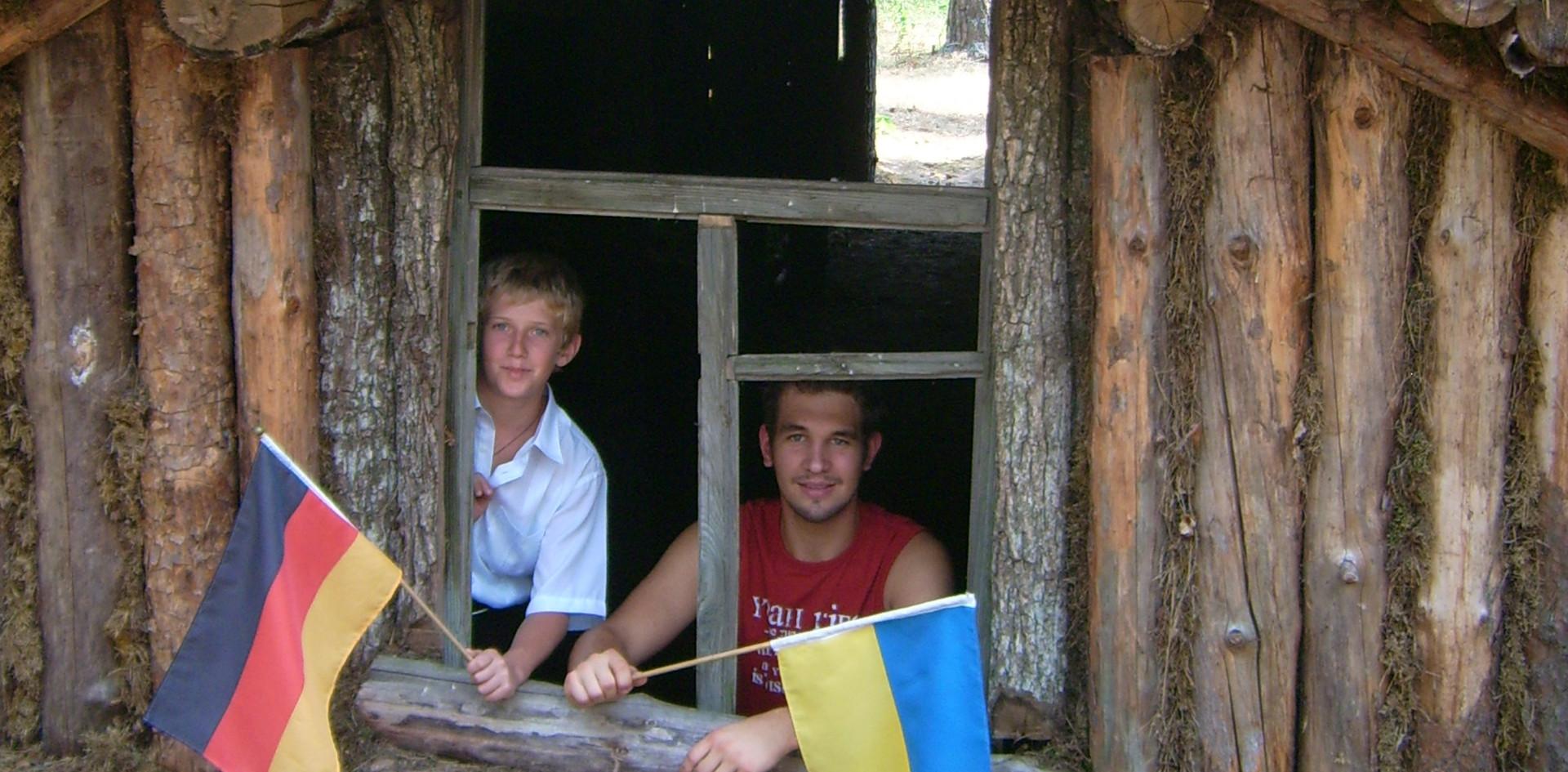Ein ukrainischer und ein deutscher Jugendlicher schwenkten 2010 in einem Partisanenunterstand im Wald von Jelino die Fahne des jeweils anderen Landes
