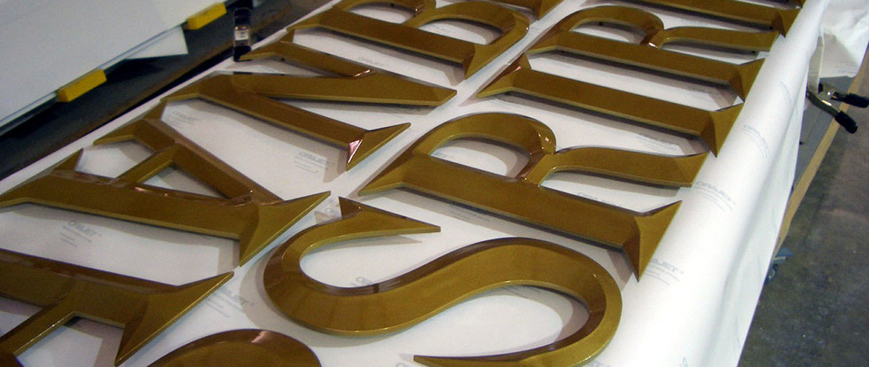 After several rounds of priming and sanding, the letters are painted with a high gloss metallic gold finish before we apply the gold leaf.