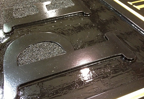 A thick adhesive mixture is carefully brushed into the recessed areas of the background.