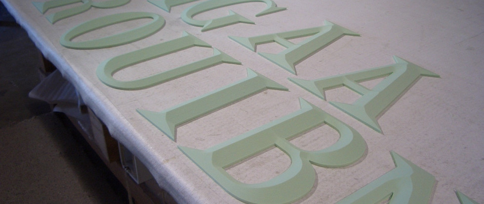 3-D bevel face letters made of high density urethane. These bevel face letters were cut out on our CNC router.  The raw HDU is light green and very porous. They get a thorough hand sanding before priming.